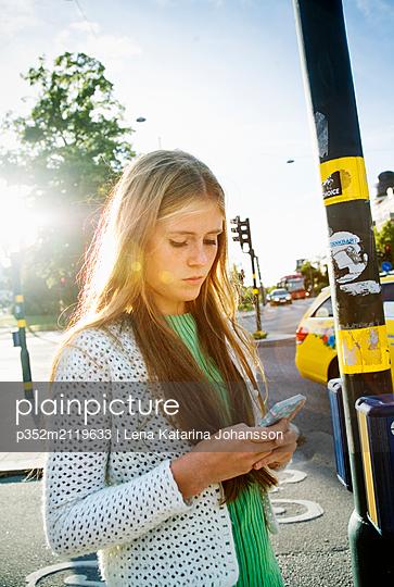 Teenage girl (16-17) texting - p352m2119633 by Lena Katarina Johansson