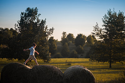 Playful boy walking on hay bales at field - p1166m1512477 by Cavan Images