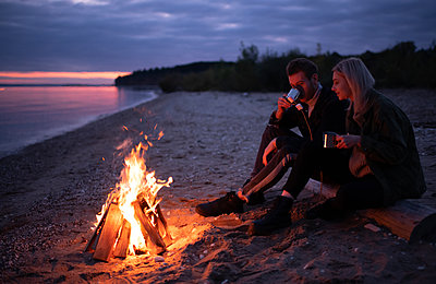 Happy couple drinking tea with marshmallows near bonfire - p1166m2235291 by Cavan Images