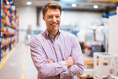 Portrait of smiling businessman in factory - p300m1562924 by Daniel Ingold
