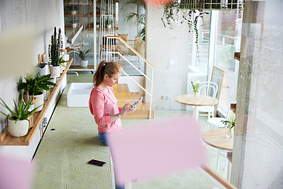 Woman using digital tablet while leaning on countertop at home - p300m2266093 by Jo Kirchherr