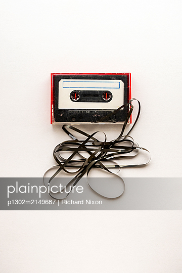 Old Audio Cassette in a red case with tape unravelling from it - p1302m2149687 by Richard Nixon