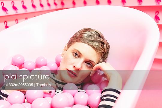 Frau liegt in Badewanne mit pinkfarbenen Plastikbällen - p1332m2055035 von Tamboly