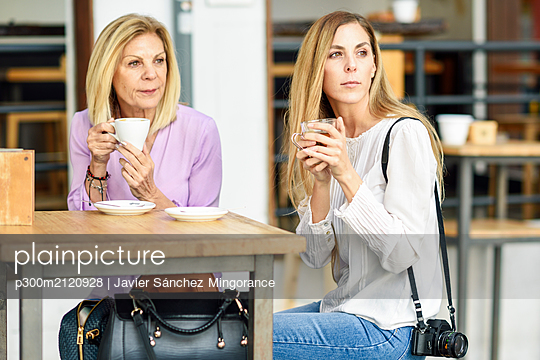 Mature woman with her daughter drinking coffee and tea sitting at an outdoor table in a cafe - p300m2120928 by Javier Sánchez Mingorance