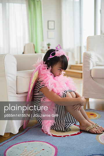 Filipino girl playing dress-up in living room