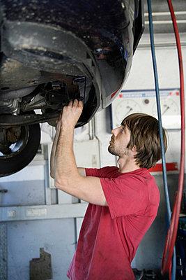 Germany, Ebenhausen, Mechatronic technician working in car garage - p30020020f by Tom Chance