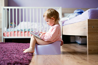 Toddler sitting on potty playing with digital tablet - p300m1120856f by HalfPoint