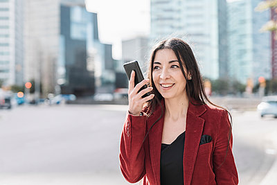 Smiling businesswoman talking on smart phone in city - p300m2265925 by COROIMAGE