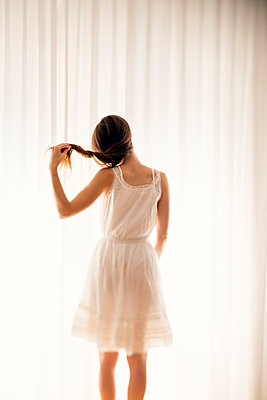 Young woman playing with her hair in front of a white curtain, back view - p300m980726f by Biederbick&Rumpf