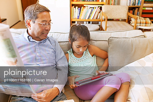 Grandfather and granddaughter looking at digital tablet on sofa at home - p1166m1163180 by Cavan Images