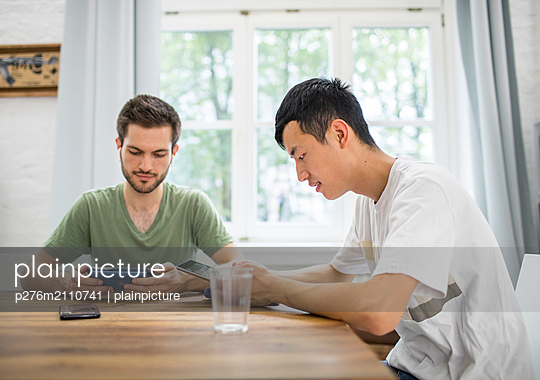 two young men busy working - p276m2110741 by plainpicture