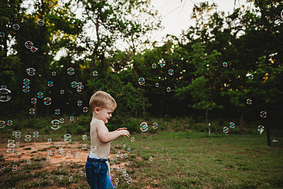Side view of shirtless baby boy playing with bubbles while standing at park - p1166m2009741 by Cavan Images