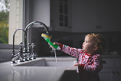 Cute baby girl holding cleaning brush in sink at home - p1166m2033932 by Cavan Images