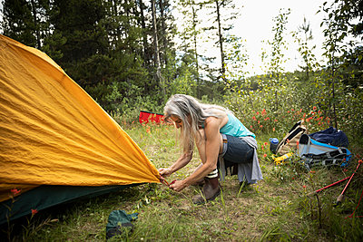 Mature woman setting up tent at forest campsite - p1192m2017195 by Hero Images