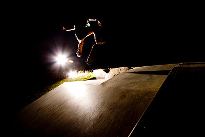 A skater flips his skateboard up a ramp under the lights at the skatepark in Whitefish, Montana. - p1424m1501290 by Noah Couser