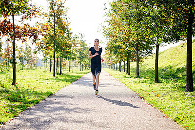 Young woman running in a park - p300m2004312 by Markus Mielek