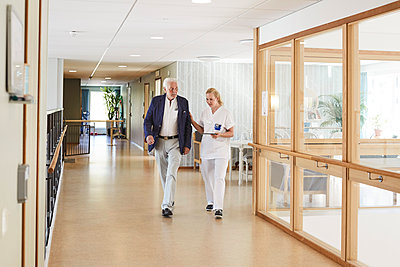 Full length of female nurse and senior male patient walking in hospital corridor - p426m1494029 by Maskot
