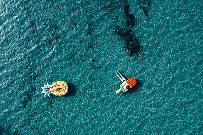Two women on air mattress in the sea, drone photography - p713m2289215 by Florian Kresse
