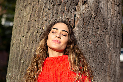 Young woman with closed eyes leaning against tree - p975m2222115 by Hayden Verry