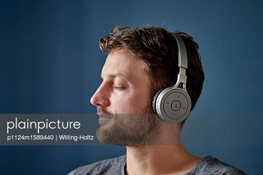 Junger Mann mit Kopfhörer hört Musik - p1124m1589440 von Willing-Holtz