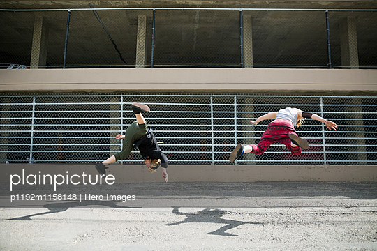 Young man doing parkour against fence in urban alley