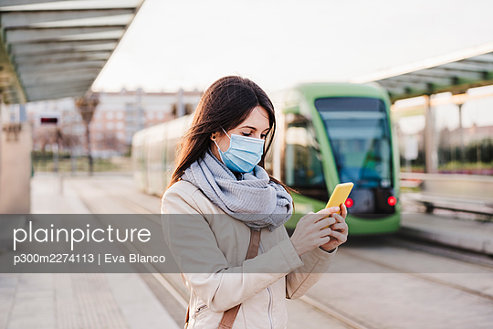 Woman using mobile phone while standing on railway platform during COVID-19 - p300m2274113 by Eva Blanco