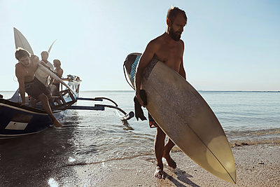 Adult men carrying surfboards while unloading vessel - p1166m2157331 by Cavan Images