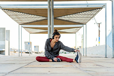 Sportive young woman with headphones during workout, stretching leg - p300m2083079 by VITTA GALLERY