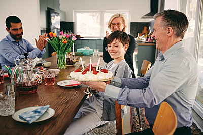 Smiling boy with grandparents and father with birthday cake at table - p426m1580219 by Maskot