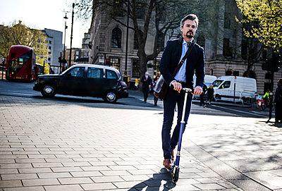 Businessman on scooter, London, UK - p429m1418028 by Bonfanti Diego