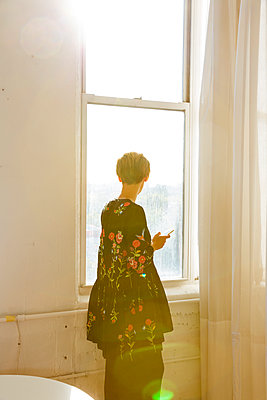 Frau mit Handy am Fenster - p432m1181452 von mia takahara