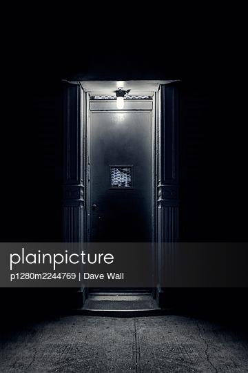 Illuminated metal door at night - p1280m2244769 by Dave Wall