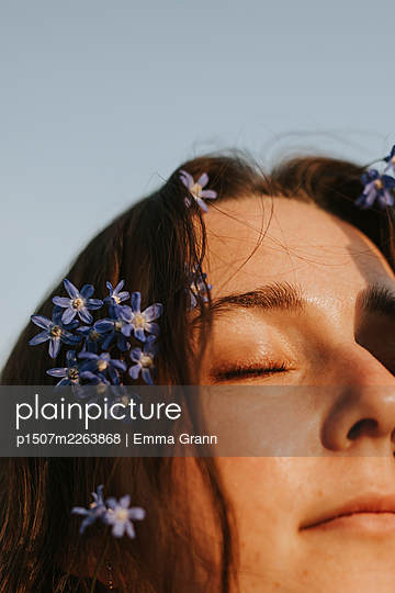 Woman with blue flowers in hair, portrait - p1507m2263868 by Emma Grann
