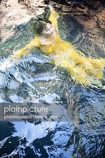Frau in gelbem Kleid im See - p1640m2259932 von Holly & John