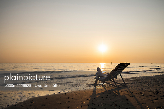 Young woman relaxing while sitting on folding chair at beach against clear sky during sunset - p300m2226529 by Uwe Umstätter