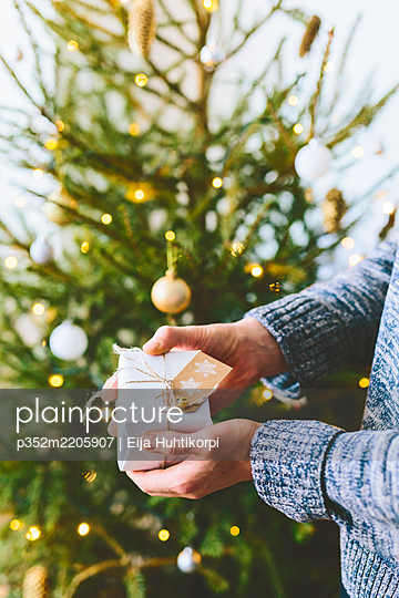 Finland, Man holding christmas gift against christmas tree - p352m2205907 by Eija Huhtikorpi