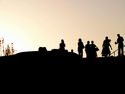 Silhouette of people beside a fountain - p1072m830492 by Clive Branson