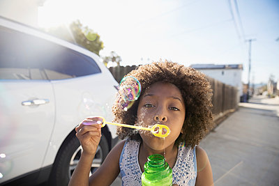 Portrait African American girl blowing bubbles with bubble wand in sunny driveway - p1192m1418604 by Hero Images