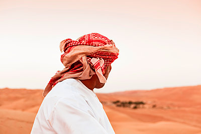 Bedouin in National dress standing in the desert, rear view, Wahiba Sands, Oman - p300m2104317 by Valentin Weinhäupl