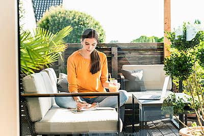 Young woman sitting on couch on terrace with healthy drink and notebook - p300m2121855 by Uwe Umstätter