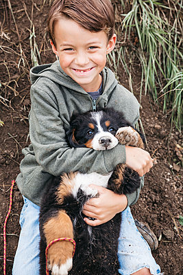 Boy playing with his Bernese mountain dog in the garden - p300m2143803 von Epiximages