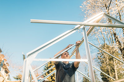 Man building greenhouse in yard during sunny day against clear blue sky - p300m2198703 by Gustafsson