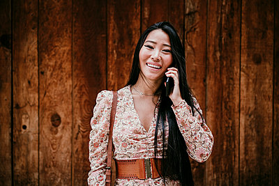Woman talking on smart phone by wooden door - p300m2274135 by Eva Blanco