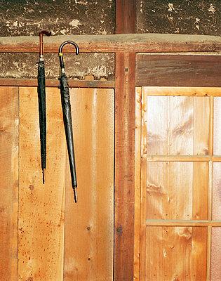 Zwei Regenschirme hängen an Wand - p3880118 von Bill Davies