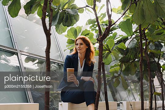 Businesswoman having a break in a modern office building - p300m2155358 by Joseffson