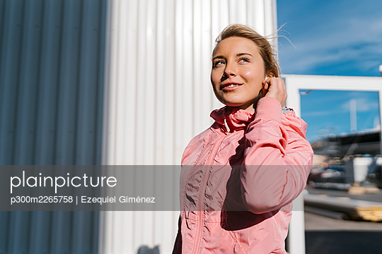 Smiling sportswoman looking away while standing by wall - p300m2265758 by Ezequiel Giménez