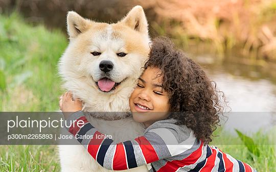 Smiling boy embracing dog in nature - p300m2265893 by Jose Carlos Ichiro