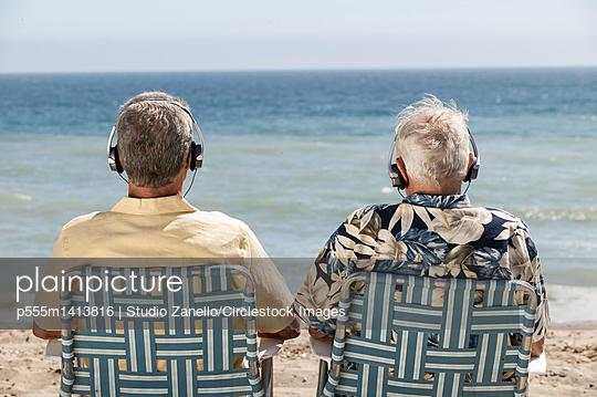 Older men listening to headphones on beach