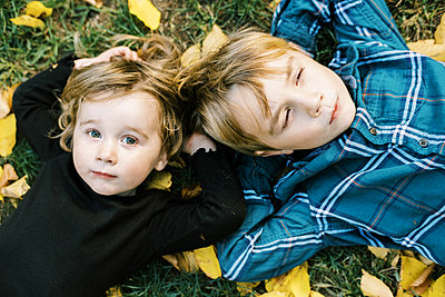 Happy siblings lying on the ground with yellow leaves around them - p1166m2216919 by Cavan Images
