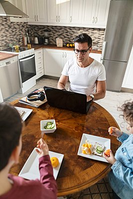 High angle view of siblings eating orange fruit while father working by table at home - p426m2186467 by Kentaroo Tryman